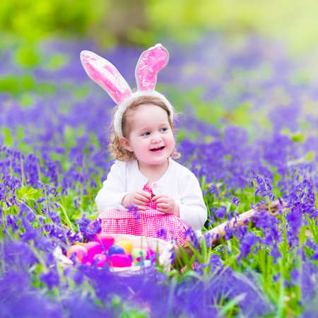 hunts: Adorable toddler girl with bunny ears having fun at Easter egg hunt in a beautiful forest with first spring flowers