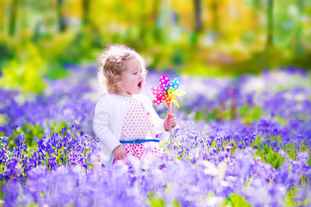 Adorable little girl with curly hair wearing a white dress playing with a wind toy having fun on a walk in a beautiful spring forest with blue bell flowers