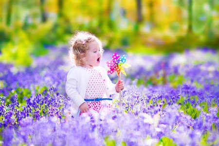 flores moradas: Ni�a adorable con el pelo rizado que llevaba un vestido blanco jugando con un juguete de cuerda que se divierte en un paseo en un hermoso bosque de la primavera con las flores azules de campana
