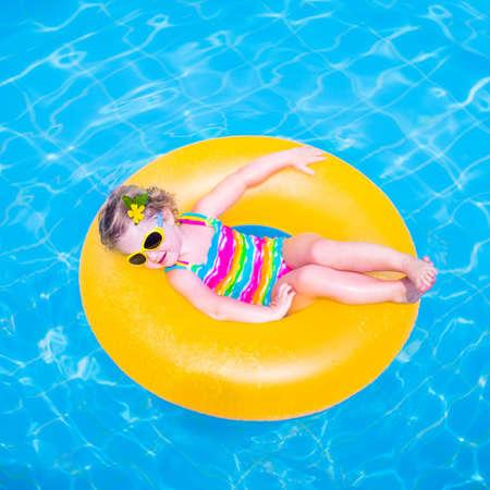 ni�as peque�as: Ni�a ni�o divertido lindo en un traje de ba�o y gafas de sol de colores relajantes en un anillo de juguete inflable flota en una piscina que se divierten durante las vacaciones de verano en un resort tropical Foto de archivo
