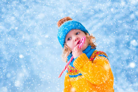 Adorable little girl, cute toddler in a blue knitted hat and yellow nordic sweater, eating Christmas red sugar candy and playing with snow catching snowflakes having fun outdoors in a beautiful winter park