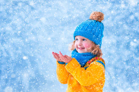 Adorable little girl, cute toddler in a blue knitted hat and yellow nordic sweater, playing with snow catching snowflakes having fun outdoors in a beautiful winter park