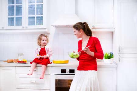 Jonge moeder en haar schattige dochter, leuke grappige peuter meisje in een rode jurk, het bakken van een taart samen de voorbereiding van een gezonde lunch in een witte zonnige keuken
