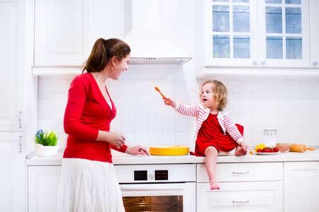 cooking: Joven madre y su hija adorable, ni�a ni�o divertido lindo en un vestido rojo, hornear un pastel juntos preparando el almuerzo saludable en una cocina blanca soleado