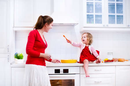 Young mother and her adorable daughter, cute funny toddler girl in a red dress, baking a pie together preparing healthy lunch in a white sunny kitchen