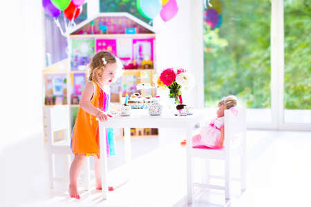 doll house: Adorable toddler girl with curly hair wearing a colorful dress on her birthday playing tea party with a doll, toy dishes, cup cakes and muffins in a sunny room with window
