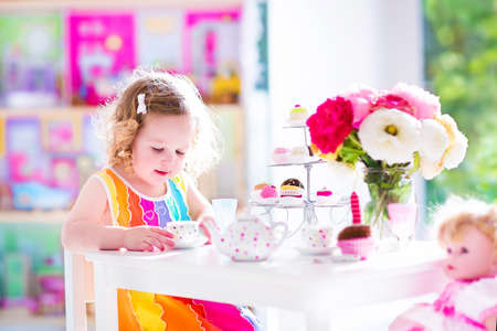 house party: Adorable toddler girl with curly hair wearing a colorful dress on her birthday playing tea party with a doll, toy dishes, cup cakes and muffins in a sunny room with window