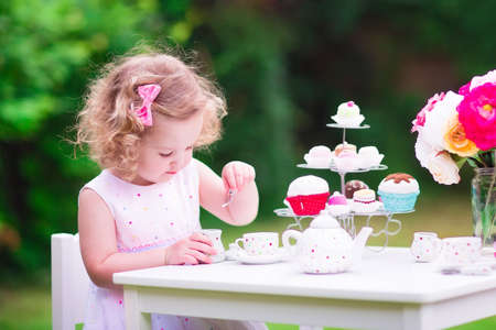 Adorable funny toddler girl with curly hair wearing a colorful dress on her birthday playing tea party with a teddy bear doll, toy dishes, cup cakes and muffins in a sunny summer garden