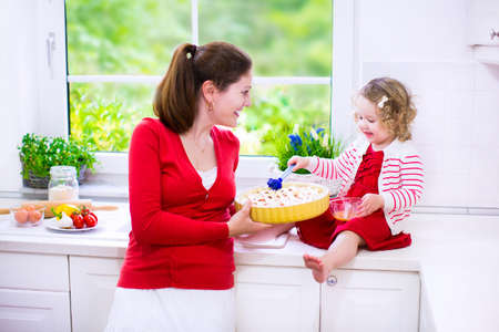 Young mother and her adorable daughter, cute funny toddler girl in a red dress, baking a pie together preparing healthy lunch in a white sunny kitchen with window photo
