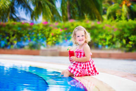Beautiful little girl, cute toddler with curly hair wearing a red summer dress, sitting at a swimming pool drinking water melon juice with fresh fruit having fun during family vacation in a tropical resort
