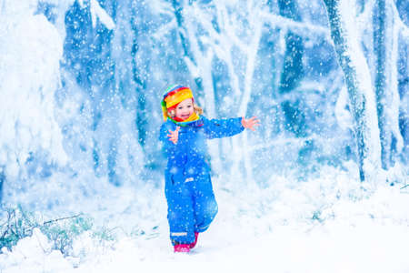 Happy laughing child, cute toddler girl in a colorful snowsuit and hat, running in a snowy winter park catching snow flakes photo
