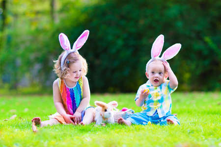Two little children, cute curly toddler girl and funny baby boy wearing bunny ears having fun at Easter egg hunt playing with basket and toy rabbit in a sunny spring garden