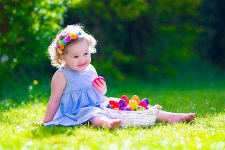 巻き毛が楽しいイースターエッグ ハント リラックスできる庭で日当たりの良い春の日の間に青い夏のドレスを着てかわいい幼児女の子