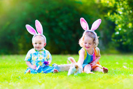 baby rabbit: Two little children, cute curly toddler girl and funny baby boy wearing bunny ears having fun at Easter egg hunt playing with basket and toy rabbit in a sunny spring garden