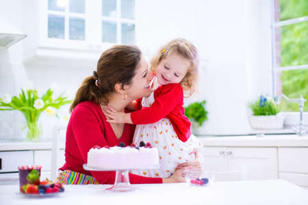 happy home: Happy family, young mother and her adorable little daughter, cute curly toddler girl in a red dress, baking fresh strawberry cream cake with fruit and berry in a white kitchen on a sunny summer day