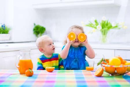 jugo de frutas: Linda ni�a divertida y beber chico adorable beb� reci�n exprimido zumo de naranja para el desayuno saludable en una cocina blanca con ventana en una soleada ma�ana de verano
