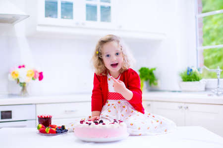 finger licking: Adorable little girl, cute curly toddler in a red dress, baking and trying fresh strawberry cream cake with fruit and berry in a white kitchen on a sunny summer day