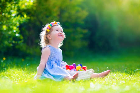 Cute little toddler girl with curly hair wearing a blue summer dress having fun during Easter egg hunt relaxing in the garden on a sunny spring day