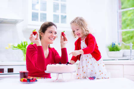 Happy family, young mother and her adorable little daughter, cute curly toddler girl in a red dress, baking fresh strawberry cream cake with fruit and berry in a white kitchen on a sunny summer day photo