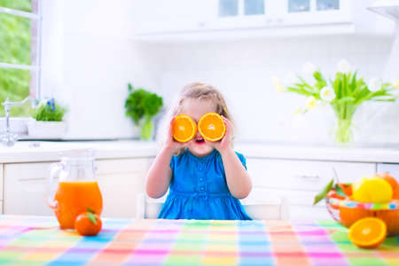 citrus family: Cute funny little girl drinking freshly squeezed orange juice for healthy breakfast in a white kitchen with window on a sunny summer morning Stock Photo