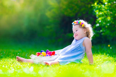 Cute little toddler girl with curly hair wearing a blue summer dress having fun during Easter egg hunt relaxing in the garden on a sunny spring day photo