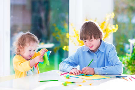school age boy: Two happy children, school age boy and little toddler girl having fun together paiting and cutting paper butterfly before easter in spring Stock Photo