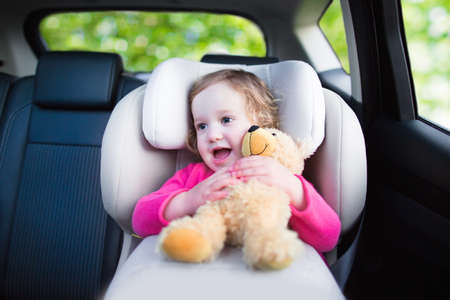 Cute curly laughing and talking toddler girl playing with a toy bear enjoying a family vacation car ride in a modern safe vehicle sitting in a baby seat with belt having fun watching out of the window photo