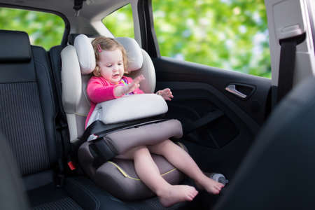 toy car: Cute curly laughing and talking toddler girl playing with a toy enjoying a family vacation car ride in a modern safe vehicle sitting in a baby seat with belt having fun watching out of the window Stock Photo