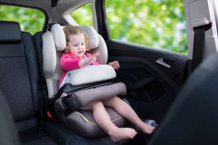 carritos de juguete: Lindo rizado riendo y hablando muchacha del ni�o que juega con un juguete disfrutando de un paseo en coche de vacaciones de la familia en un veh�culo seguro moderno, sentado en un asiento de beb� con el cintur�n de divertirse viendo por la ventana