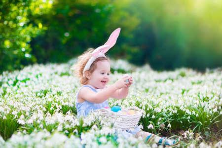 huevo blanco: Adorable ni�o ni�a rizado con orejas de conejo jugando con huevos de Pascua en una cesta blanca sentado en un jard�n soleado con primeras flores de primavera en blanco