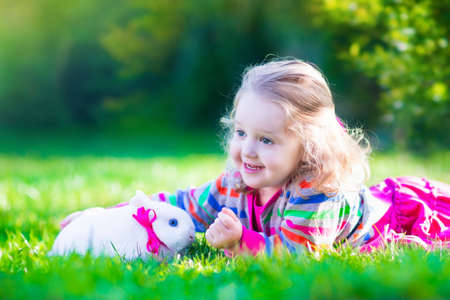 Adorable curly toddler girl playing with a real rabbit in a sunny summer garden, child feeding bunny a carrot. photo