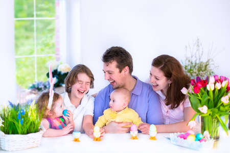 children breakfast: Happy young family with three children - teenager boy, cute little toddler girl with bunny ears and a newborn baby - enjoying Easter breakfast in a white sunny dining room with a big garden view window