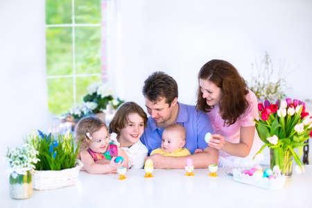 niños desayunando: Joven familia feliz con tres hijos - muchacho adolescente, niña linda niño con orejas de conejo y un bebé recién nacido - de disfrutar del desayuno Pascua en un soleado comedor blanco con una ventana de vista amplio jardín