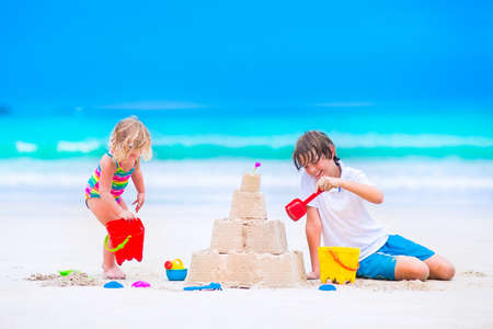 castle buildings: laughing boy and a little toddler girl in colorful swimming suit building sand castle and playing with toys on exotic tropical beach Stock Photo