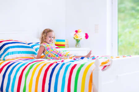 baby bedroom: Cute little curly toddler girl in a colorful dress jumping on a big white bed laughing and having fun on a sunny weekend morning in a bedroom