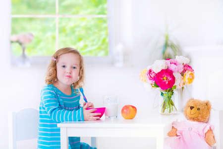 Funny cute little girl in a blue dress eating healthy breakfast - fruit, cereal and milk, feeding her toy bear in a white sunny kitchen photo