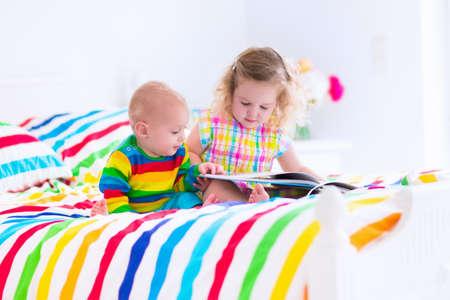 rizado niña niño y un bebé divertido, hermano y hermana, leyendo un libro en una habitación soleada en una cama blanca de madera con ropa de cama colorida del arco iris