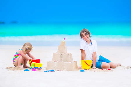 children sandcastle: laughing boy and a little toddler girl in colorful swimming suit building sand castle and playing with toys on exotic tropical beach Stock Photo
