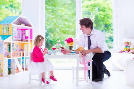 fiesta familiar: padre joven y su peque�a hija, muchacha linda del ni�o rizado llevaba un vestido, jugando junto con la casa de mu�ecas, que tienen fiesta de t� de juguete en un vivero asoleado blanco