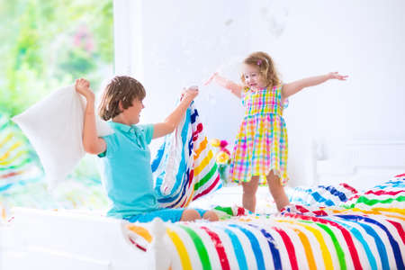 sleepover: happy laughing boy and cute curly little girl having fun at pillow fight with feathers in the air jumping, laughing and giggling in a white bedroom with colorful bedding