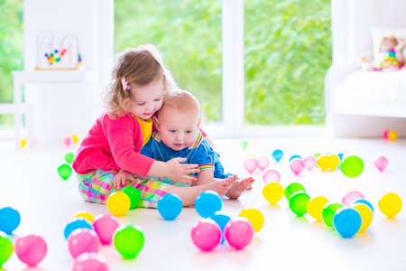 group of colourful ball: cute curly toddler girl and a funny baby boy playing together with colorful balls in a white sunny room with big window