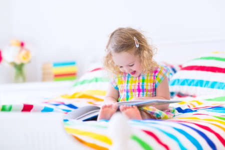 Cute curly little toddler girl reading a book sitting in a sunny bedroom on a wooden white bed with colorful rainbow bedding