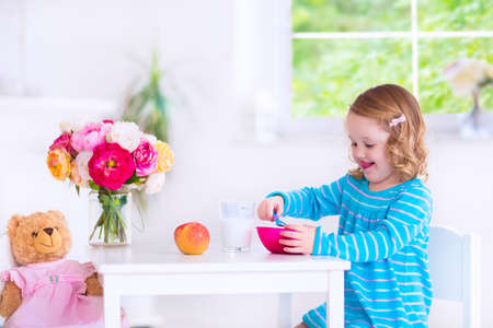 Grappig schattig klein meisje in een blauwe jurk het eten van gezond ontbijt - fruit, granen en melk, het voeden van haar speelgoed beer in een witte zonnige keuken