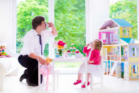 young father and his little daughter, cute curly toddler girl wearing a dress, playing together with doll house, having toy tea party in a white sunny nursery