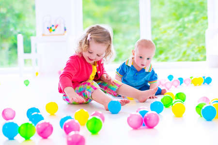 cute curly toddler girl and a funny baby boy playing together with colorful balls in a white sunny room with big window