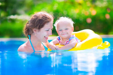 getaway: young active mother and adorable curly little baby having fun in a swimming pool Stock Photo