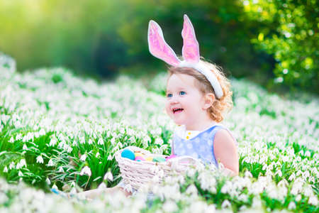 easter flowers: Adorable curly toddler girl wearing bunny ears playing with Easter eggs in a white basket sitting in a sunny garden with first white spring flowers