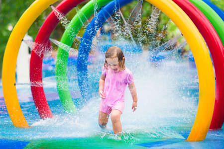 Happy little toddler girl running through a fountain having fun with water splashes in a swimming pool enjoying day trip to an aqua amusement park during summer family vacation Archivio Fotografico