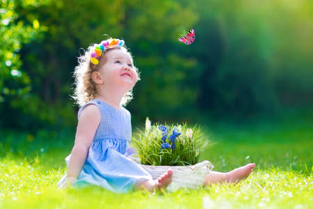 Cute little toddler girl with curly hair wearing a blue summer dress having fun watching a butterfly and flowers, relaxing in the garden on a sunny spring day