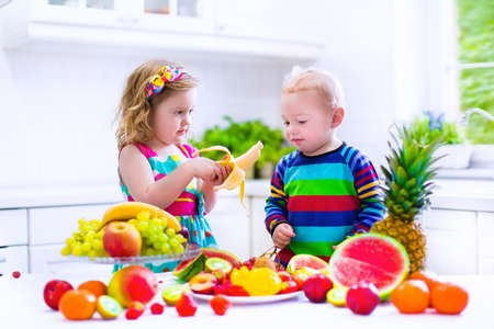 Happy little children, cute toddler girl and funny baby boy, brother and sister, eating fresh ripe fruit for healthy breakfast in a white sunny family kitchen with window photo